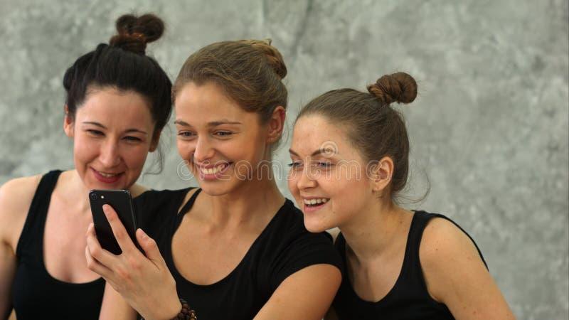 Tres mujeres jovenes que hojean Internet usando smartphone después de entrenamiento en la clase de la yoga fotografía de archivo
