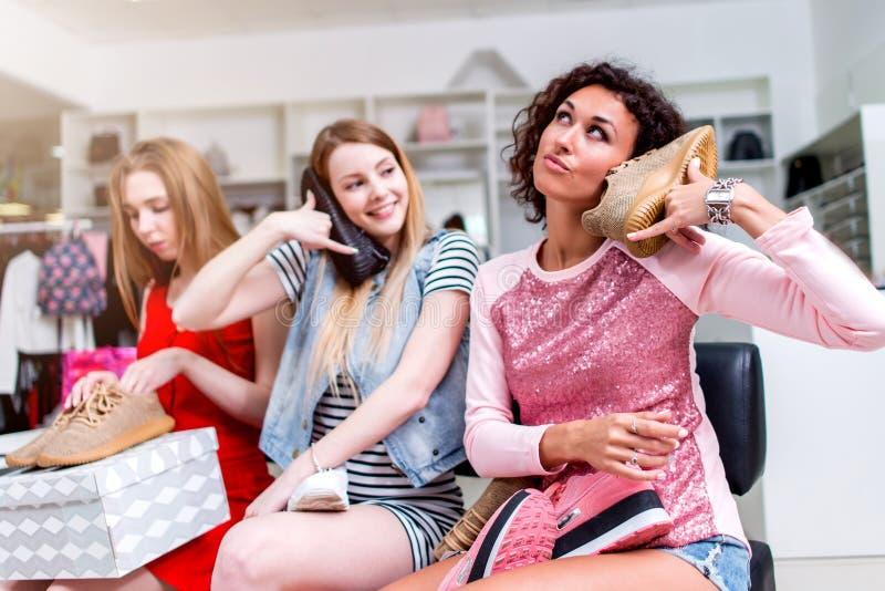 Tres mujeres jovenes que se divierten con el nuevo calzado que finge haciendo una llamada de teléfono con los zapatos que se sien imagen de archivo libre de regalías