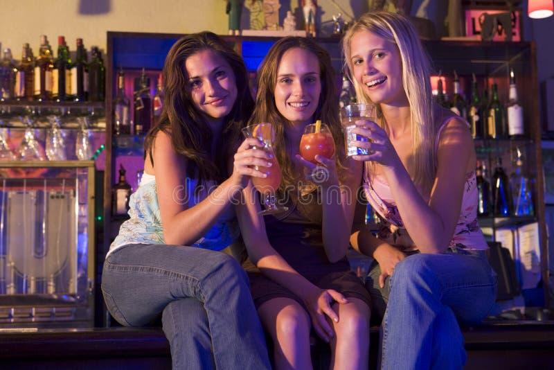 Tres mujeres jovenes que se sientan en un contador de la barra fotos de archivo libres de regalías