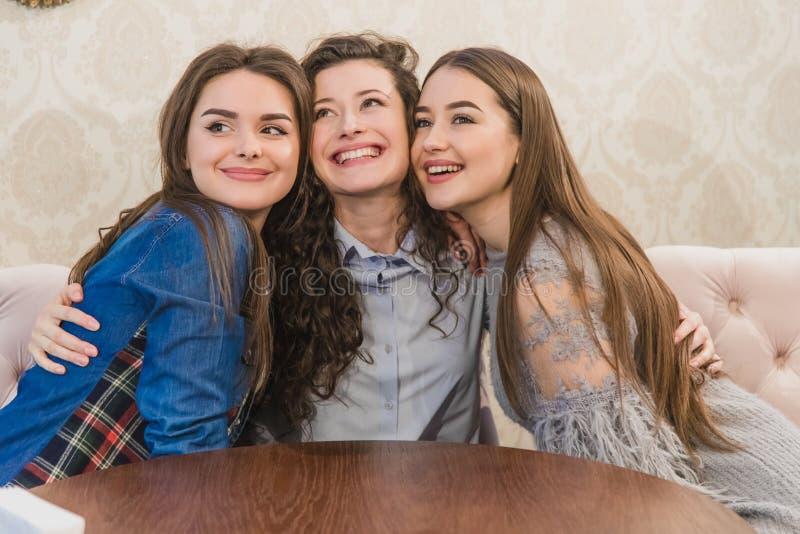 Tres mujeres jovenes que se sientan junto en pequeños cafés contra ventanas grandes y que se abrazan Chicas j?venes hermosas fotos de archivo libres de regalías