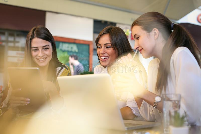 Tres mujeres jovenes que tienen conversación en café usando el top del revestimiento y fotografía de archivo
