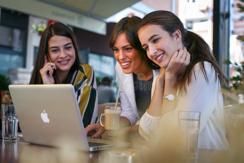 Tres mujeres jovenes que tienen conversación en café y que usan el ordenador portátil imágenes de archivo libres de regalías