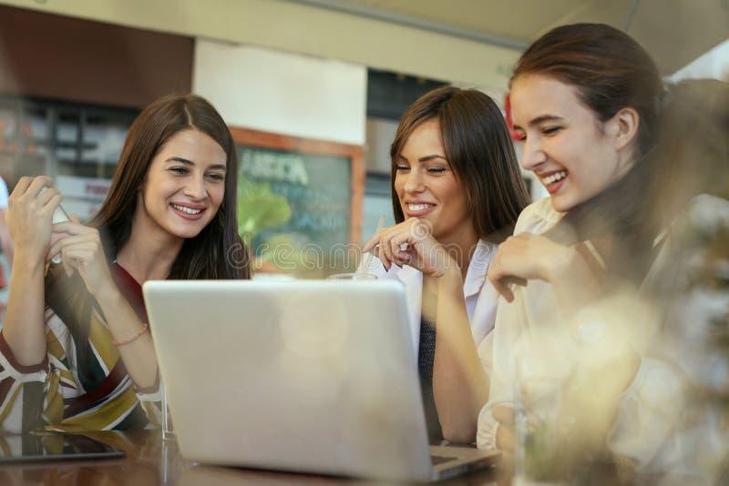 Tres mujeres jovenes que tienen conversación en café y que usan el ordenador portátil fotografía de archivo