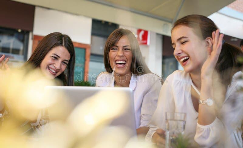 Tres mujeres jovenes que tienen conversación en café y que usan el ordenador portátil imagen de archivo libre de regalías