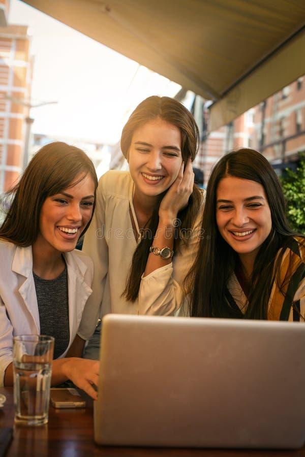 Tres mujeres jovenes que tienen conversación en café y que usan el ordenador portátil imagenes de archivo