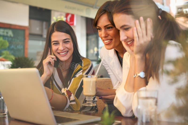 Tres mujeres jovenes que tienen conversación en café y que usan el ordenador portátil fotografía de archivo libre de regalías