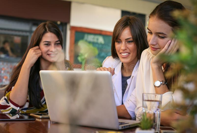Tres mujeres jovenes que tienen conversación en café y que usan el ordenador portátil imagen de archivo
