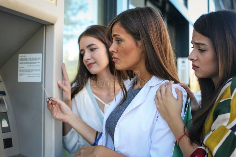 Tres mujeres jovenes tristes sobre ningún dinero en tarjeta de crédito fotos de archivo