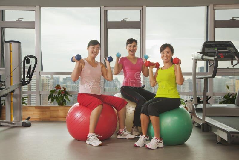 Tres mujeres maduras que ejercitan con la bola de la aptitud y que llevan a cabo pesos en el gimnasio imágenes de archivo libres de regalías