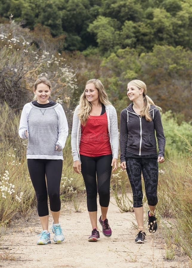 Tres mujeres que caminan y que se resuelven junto fotografía de archivo libre de regalías