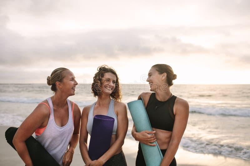 Tres mujeres que llevan las esteras de la yoga que se colocan en la playa imágenes de archivo libres de regalías