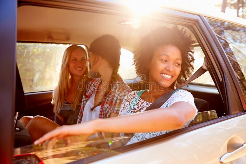 Tres mujeres que se sientan en Seat posterior del coche en viaje por carretera fotos de archivo