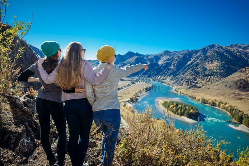 Tres mujeres se colocan en una colina y una mirada en un río de la montaña Viaje con los amigos en Altai Las muchachas abrazan y  foto de archivo libre de regalías