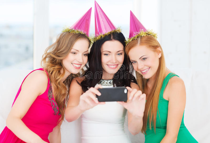 Tres mujeres sonrientes en los sombreros que se divierten con la cámara foto de archivo