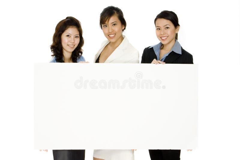 Tres mujeres y muestra en blanco imagenes de archivo