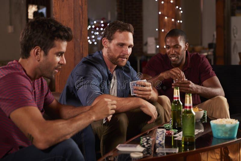 Tres naipes masculinos de los amigos y cerveza de consumición en casa foto de archivo
