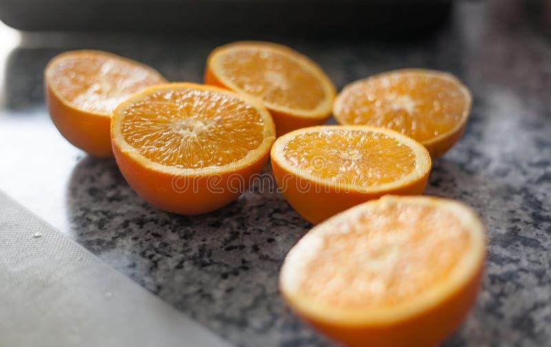 Tres naranjas cutted por la mitad en una tabla de cocina imágenes de archivo libres de regalías