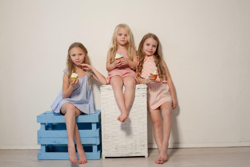 Tres niñas comen la torta dulce con la magdalena poner crema fotos de archivo