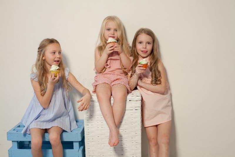 Tres niñas comen la torta dulce con la magdalena poner crema foto de archivo