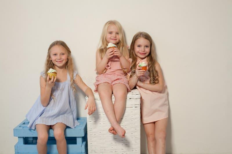 Tres niñas comen la torta dulce con la magdalena poner crema imagen de archivo libre de regalías