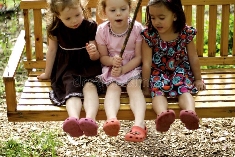 Tres niñas en el oscilación fotografía de archivo