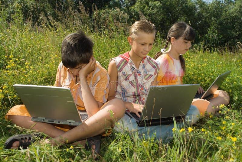 Tres niños con la computadora portátil imagenes de archivo
