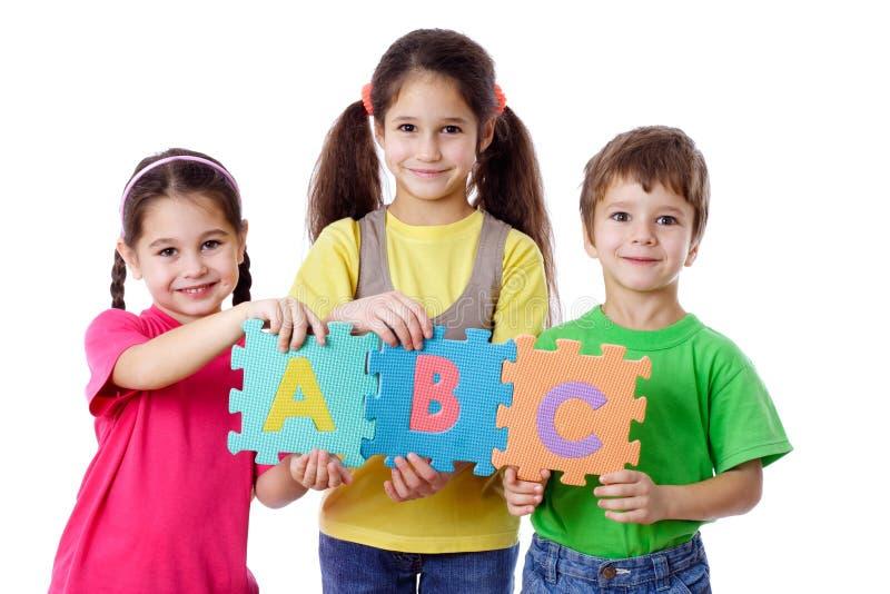 Tres niños con las cartas fotos de archivo libres de regalías