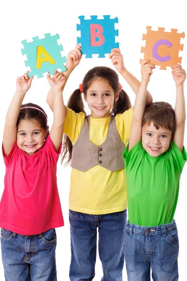 Tres niños con las letras fotografía de archivo libre de regalías