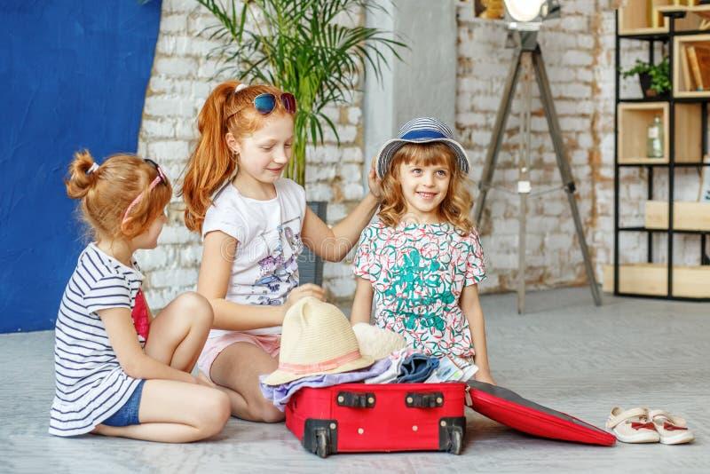 Tres niños de la diversión embalan una maleta por un día de fiesta de la playa Concepto, imagen de archivo