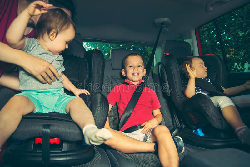 Tres niños en asiento de la seguridad del coche imagen de archivo libre de regalías