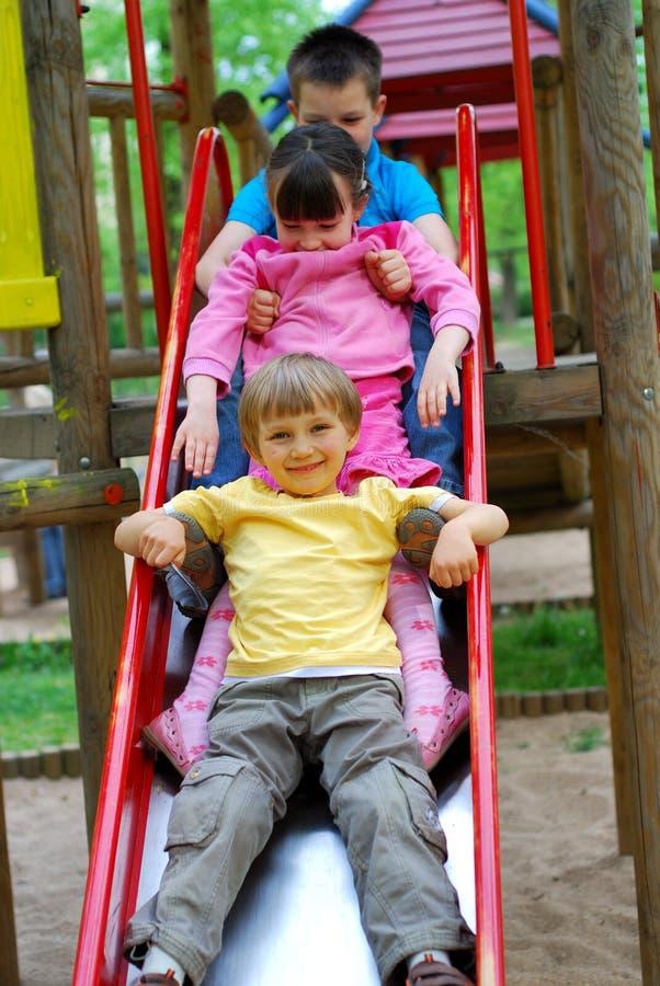 Tres niños en diapositiva imagenes de archivo