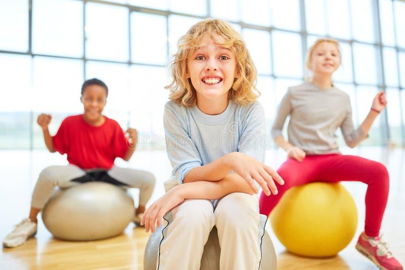 Tres niños en la educación física con la bola animosa fotografía de archivo