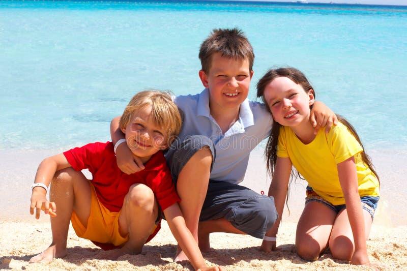 Tres niños en la playa imagen de archivo libre de regalías