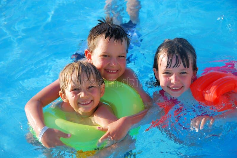 Tres niños en piscina fotografía de archivo