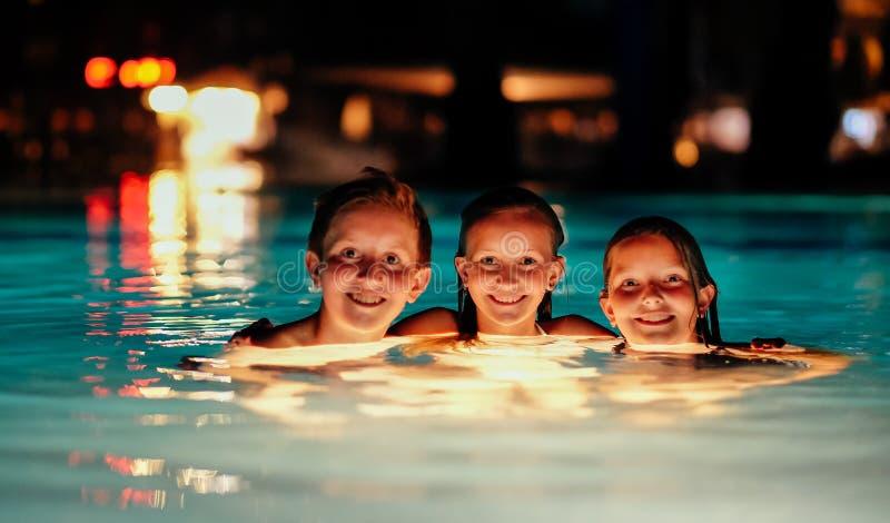 Tres niños en piscina iluminada fotos de archivo