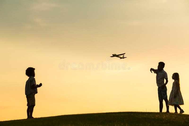 Tres niños en puesta del sol imagenes de archivo