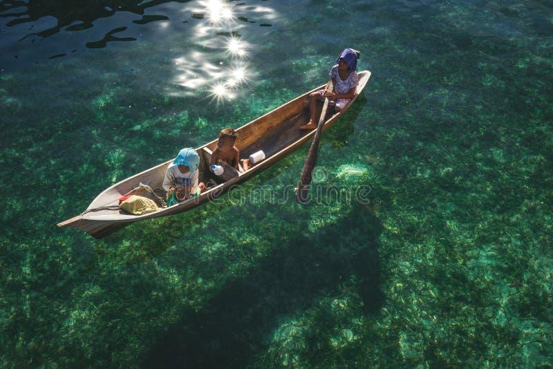 Tres niños en su barco de madera sobre el agua muy clara fotografía de archivo