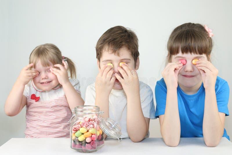 Tres niños felices cierran ojos por los caramelos cerca del tarro foto de archivo
