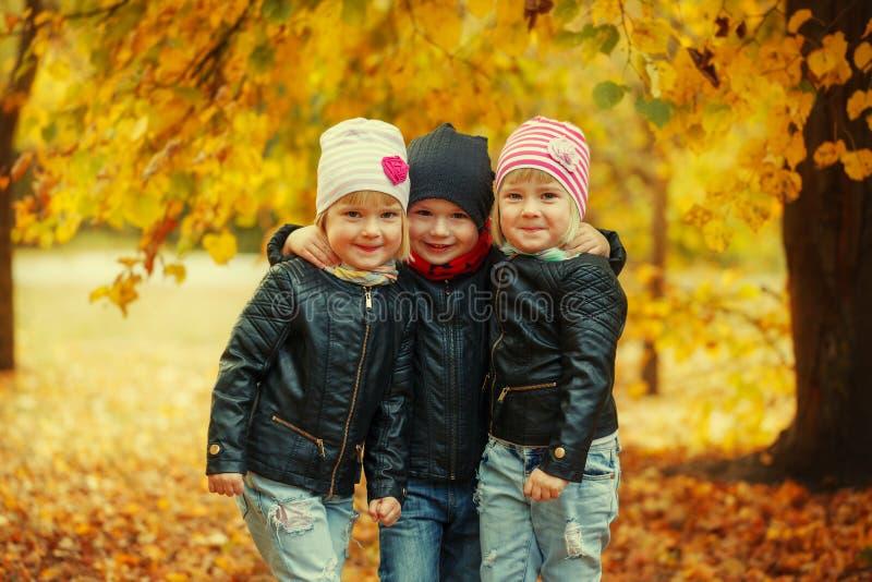 Tres niños felices de los amigos que abrazan y que ríen en parque del otoño fotos de archivo libres de regalías
