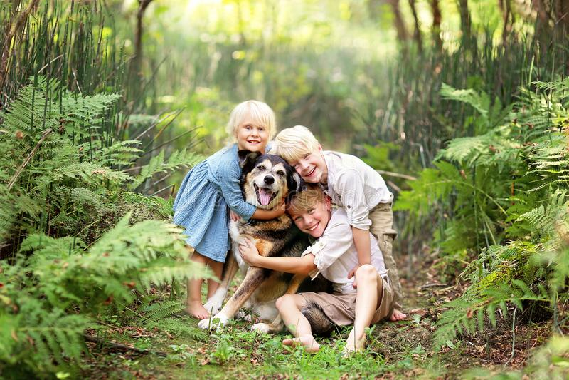 Tres niños felices Lovinglt que abraza el perro casero en el bosque imagen de archivo
