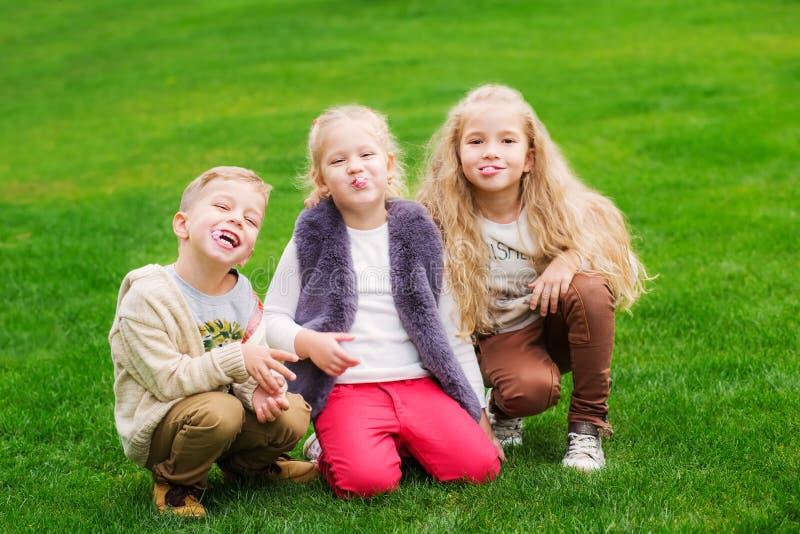 Tres niños felices mastican la goma fotografía de archivo libre de regalías