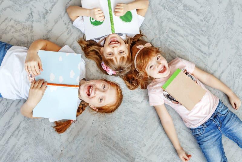 Tres niños felices mienten en el piso y leen los libros El concep fotos de archivo libres de regalías