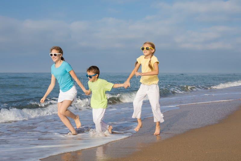 Tres niños felices que corren en la playa en el tiempo del día fotografía de archivo libre de regalías