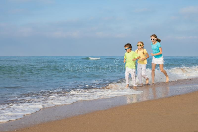Tres niños felices que corren en la playa en el tiempo del día fotografía de archivo