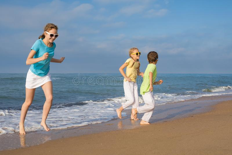 Tres niños felices que corren en la playa en el tiempo del día imagenes de archivo