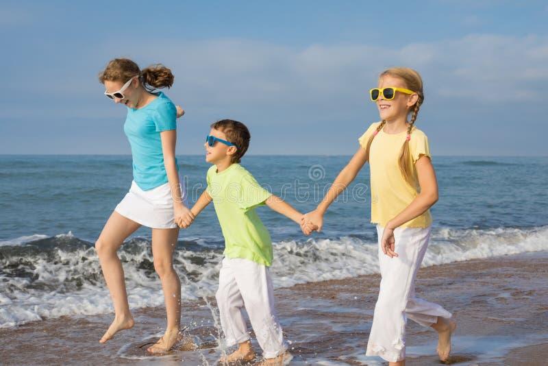 Tres niños felices que corren en la playa en el tiempo del día imagen de archivo