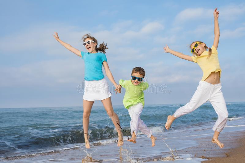 Tres niños felices que corren en la playa en el tiempo del día imagen de archivo libre de regalías