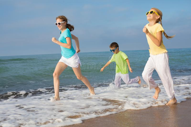 Tres niños felices que corren en la playa en el tiempo del día imágenes de archivo libres de regalías