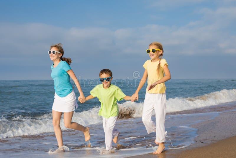 Tres niños felices que corren en la playa en el tiempo del día foto de archivo libre de regalías