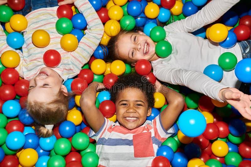 Tres niños felices que juegan en Ballpit fotografía de archivo